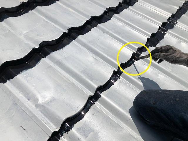刷毛を使い板金屋根の重なり部分を中塗り塗装